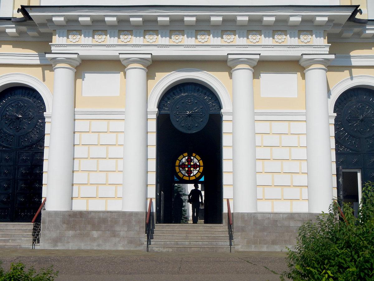 Вход на территорию Высоцкого монастыря через фасад нижнего яруса колокольни. Живописна колоннада и арка, а особенно – витраж из цветного стекла.