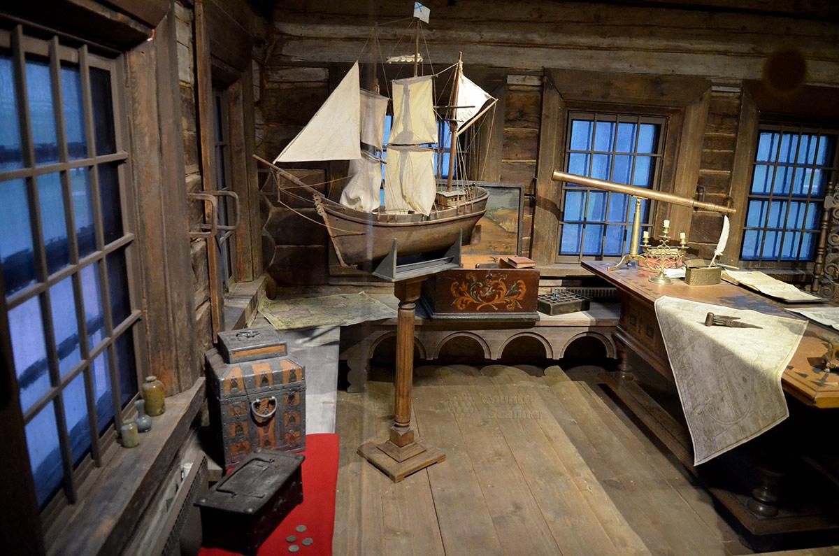 Лавки вдоль стен царского кабинета в домике Петра заняты сундучками с книгами и другими предметами занятий. В углу на стойке большая модель парусника с полным оснащением.