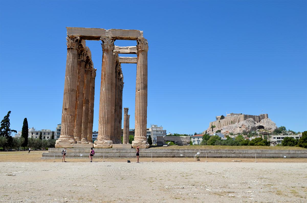 Посещающие храм Зевса Олимпийского туристы фотографируют достопримечательность со всех возможных точек. Часто в кадр попадает Акрополь – комплекс сооружений на неприступной скале.