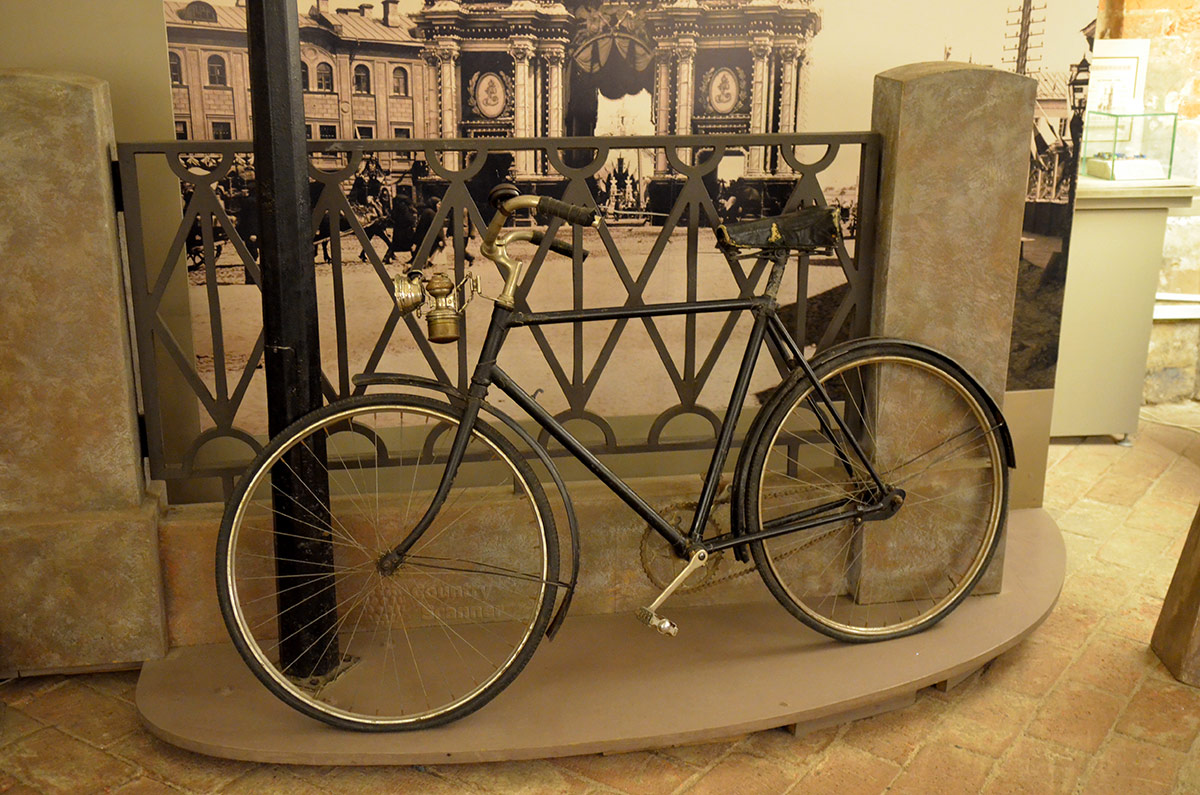 На фоне городской улицы к ограде прислонен почти современного вида велосипед. В Огни Москвы он попал ради демонстрации керосинового фонаря, не способного осветить дорогу, но хотя бы обозначающее присутствие там велосипеда.