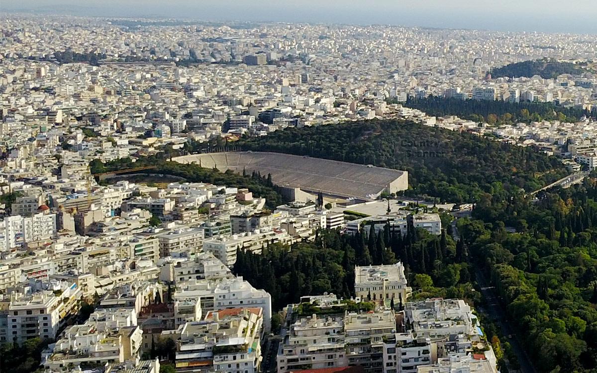 Вид с прилегающих холмов на афинский стадион Панатинаикос завораживает своей живописностью. Чаша арены окружена растительностью, далее жилая застройка до линии горизонта.