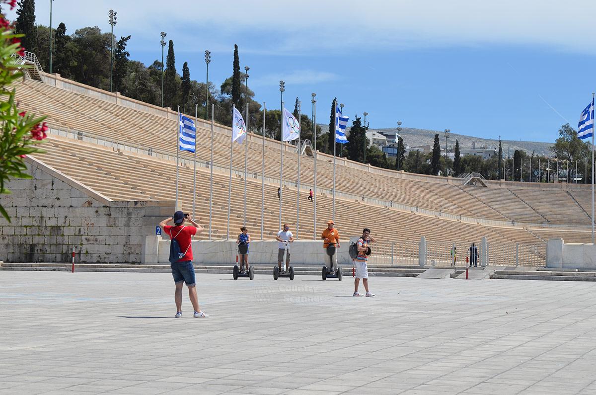 На площади перед стадионом Панатинаикос можно не только ходить пешком, здесь допустимо передвигаться более комфортными способами. Туристы используют компактные электрические скутеры.