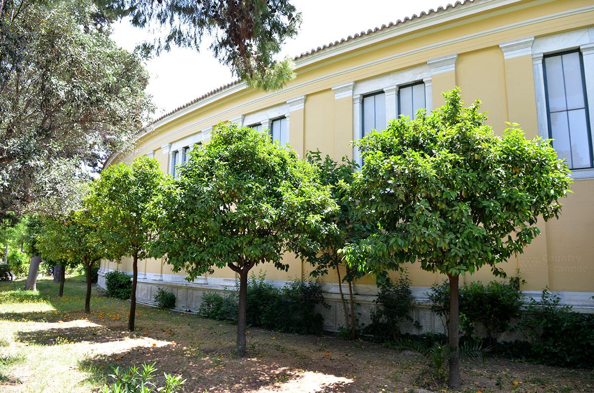 Округлая стена галереи дворца и конгресс-холла Заппейон имеет на самом деле форму подковы. Параллельно стене высажены дикие мандариновые деревья.