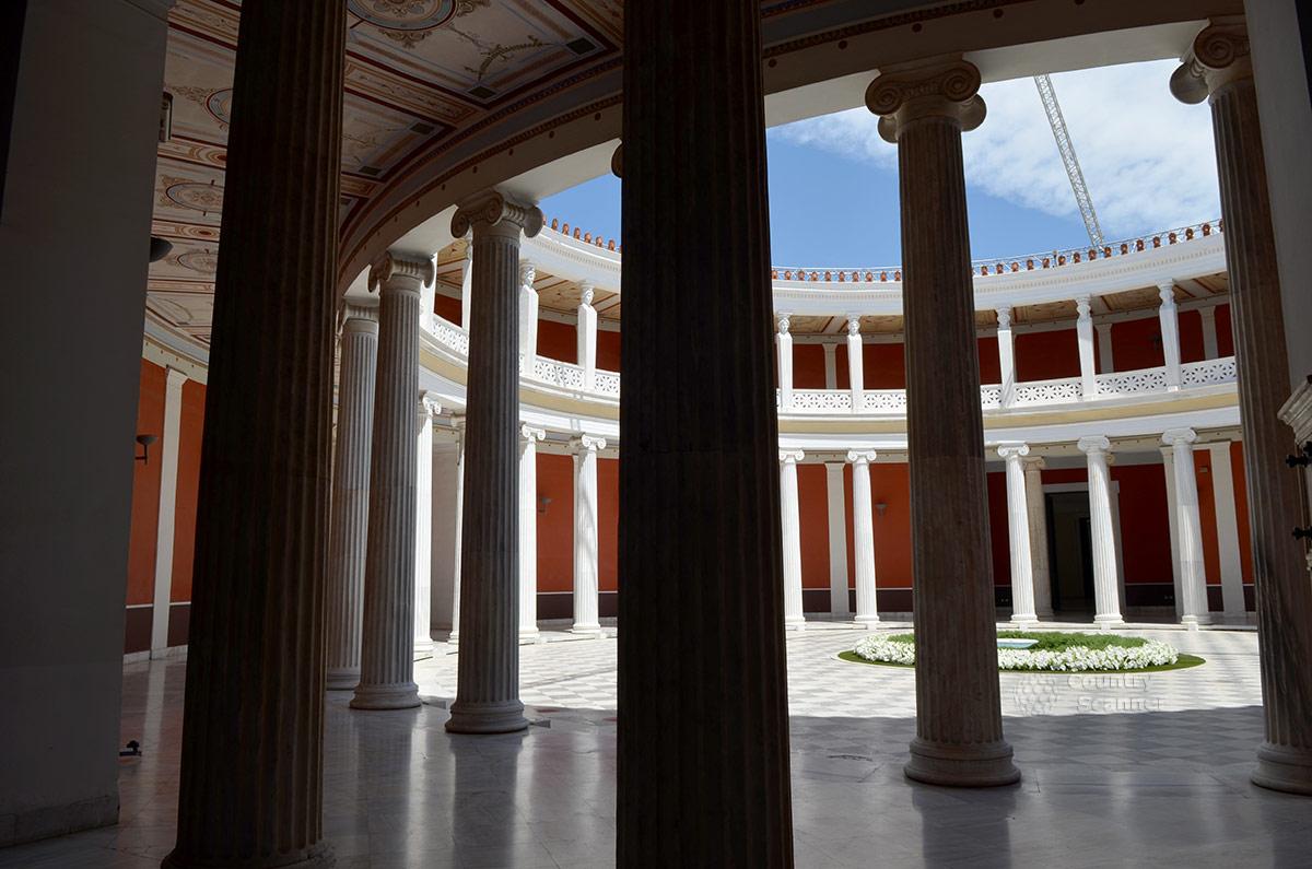 Величественная ротонда дворца Заппейон состоит из двух ярусов, разделенных перекрытием. На каждой отметке множество установленных по кругу колонн. Центр сооружения открыт солнечному свету.