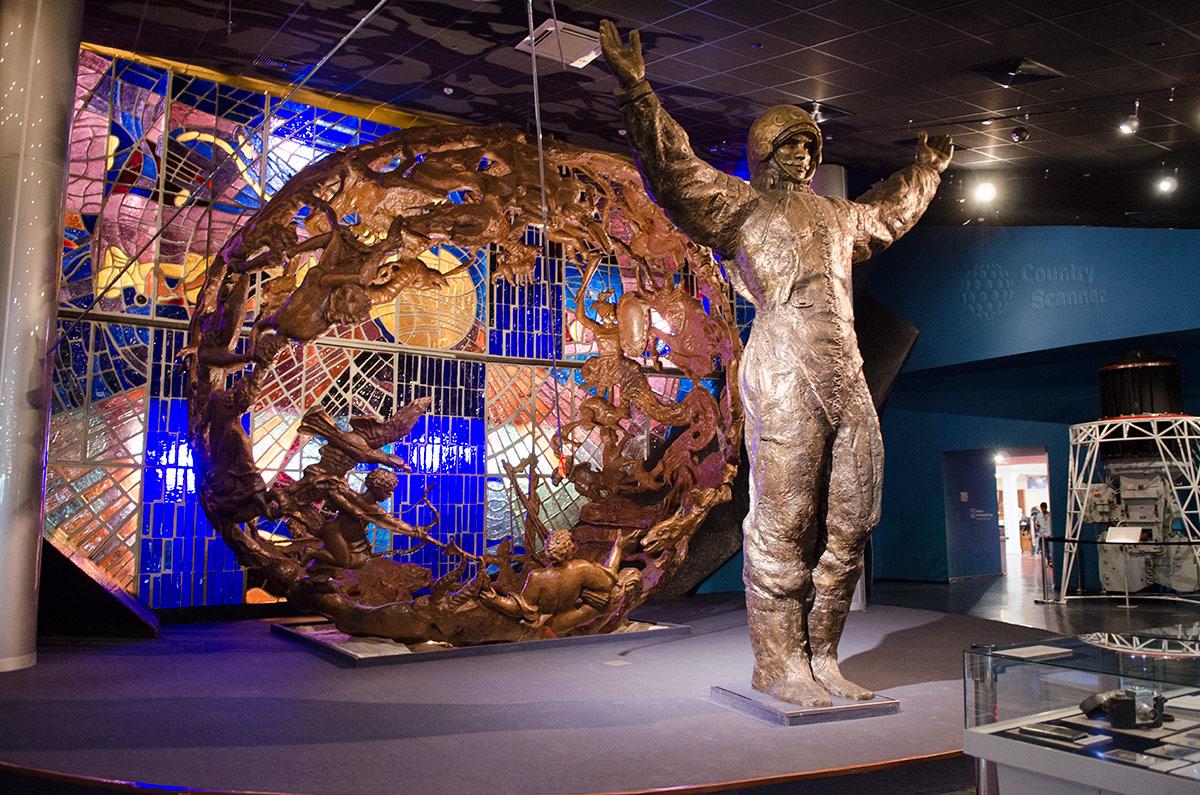 На входе в музей космонавтики посетителей встречает скульптура Юрия Гагарина с поднятыми к небу руками. На фоне красочного панно космонавт № 1 приветствует все население планеты.