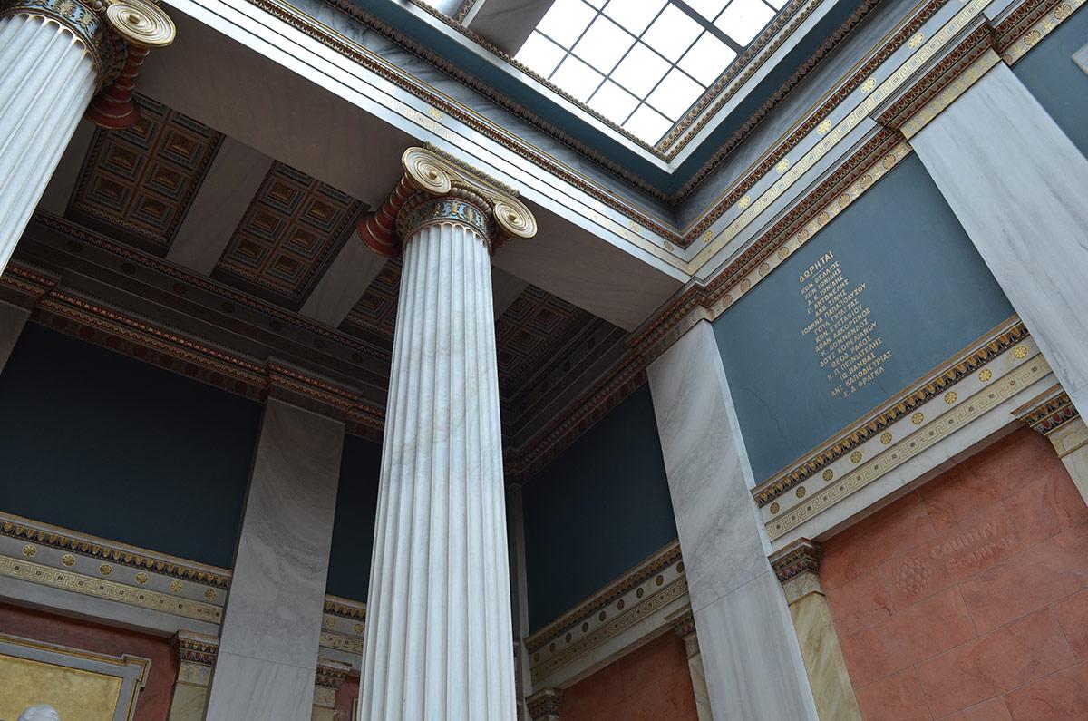 Внутри здания Национальной библиотеки Греции внимание привлекает прежде всего стеклянный потолок. Верхняя часть колонн – капители здесь уже явно принадлежат к ионическому архитектурному ордеру.