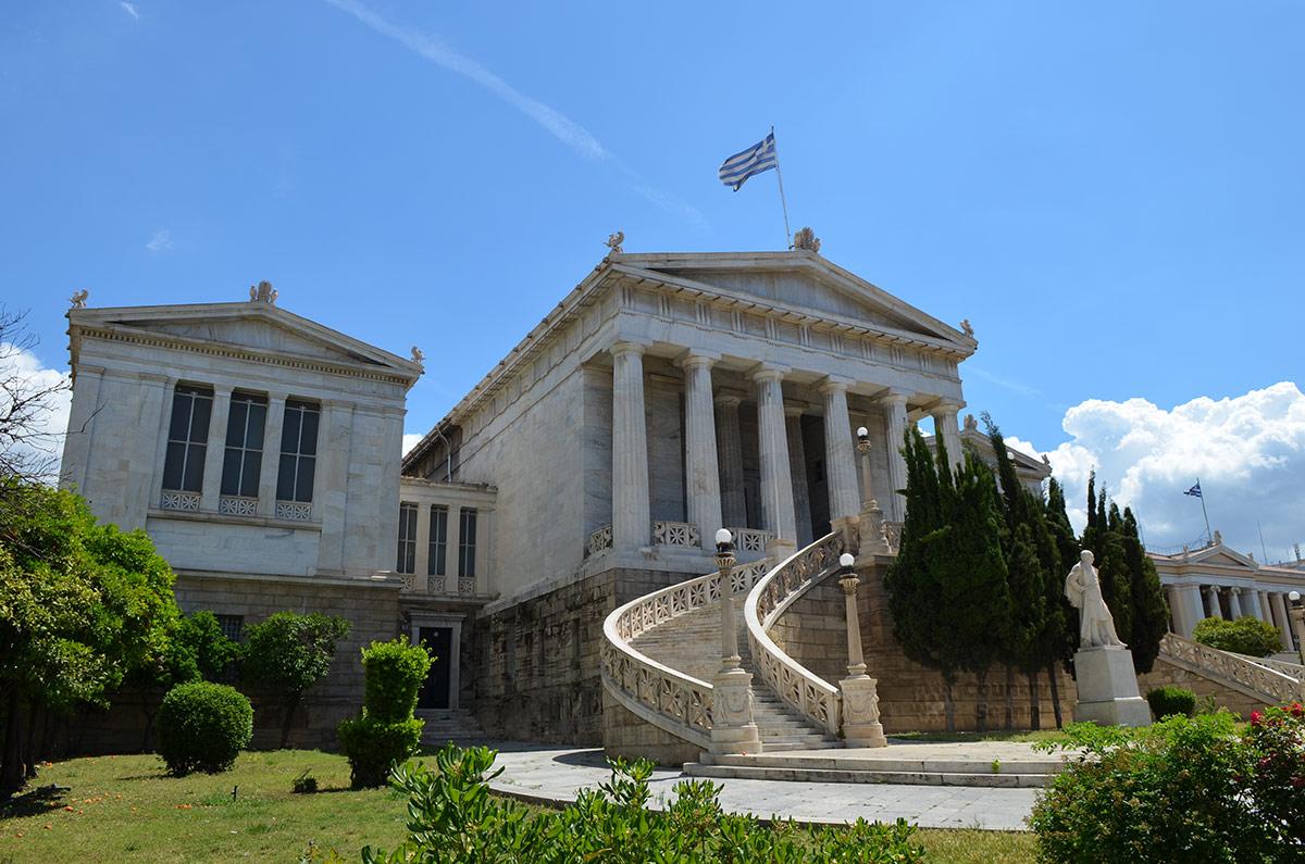 Вид от подножия здания Национальной библиотеки Греции иллюстрирует возвышенное расположение строения по отношению к окружающей местности. Флаг страны – неотъемлемая принадлежность подобных зданий.