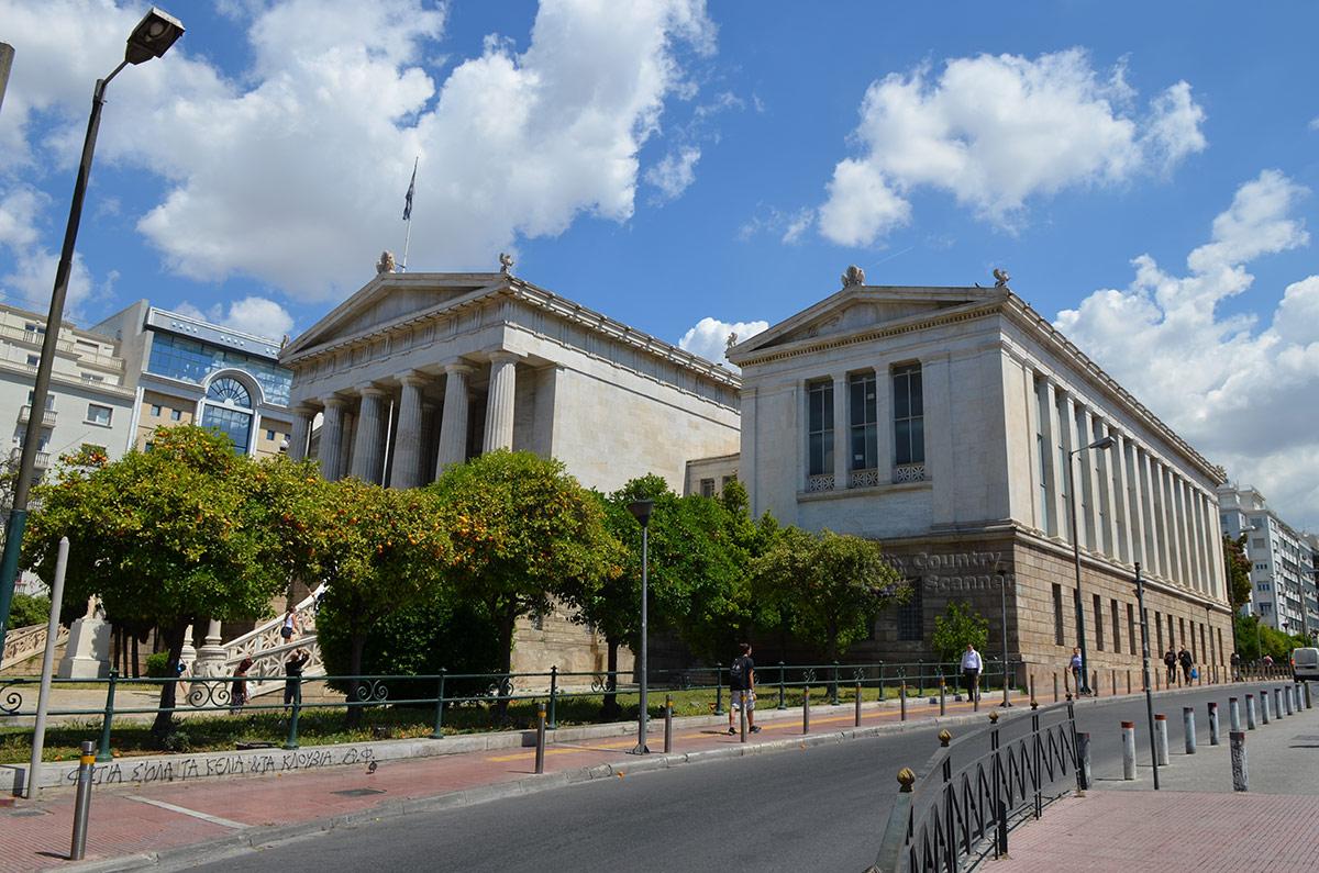 Вид со стороны прилегающей улицы позволяет рассмотреть архитектурные особенности здания Национальной библиотеки Греции. Достойна внимания высота потолков верхнего этажа флигеля, где расположен один из читальных залов.