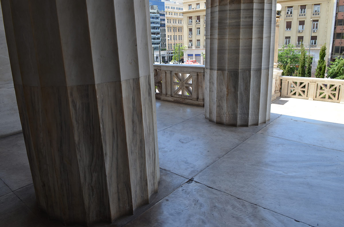 Выходящие на террасу главного здания Национальной библиотеки Греции могут рассмотреть устройство колонн. Отсутствие опорной базы под стволами выдает принадлежность к дорическому ордеру.