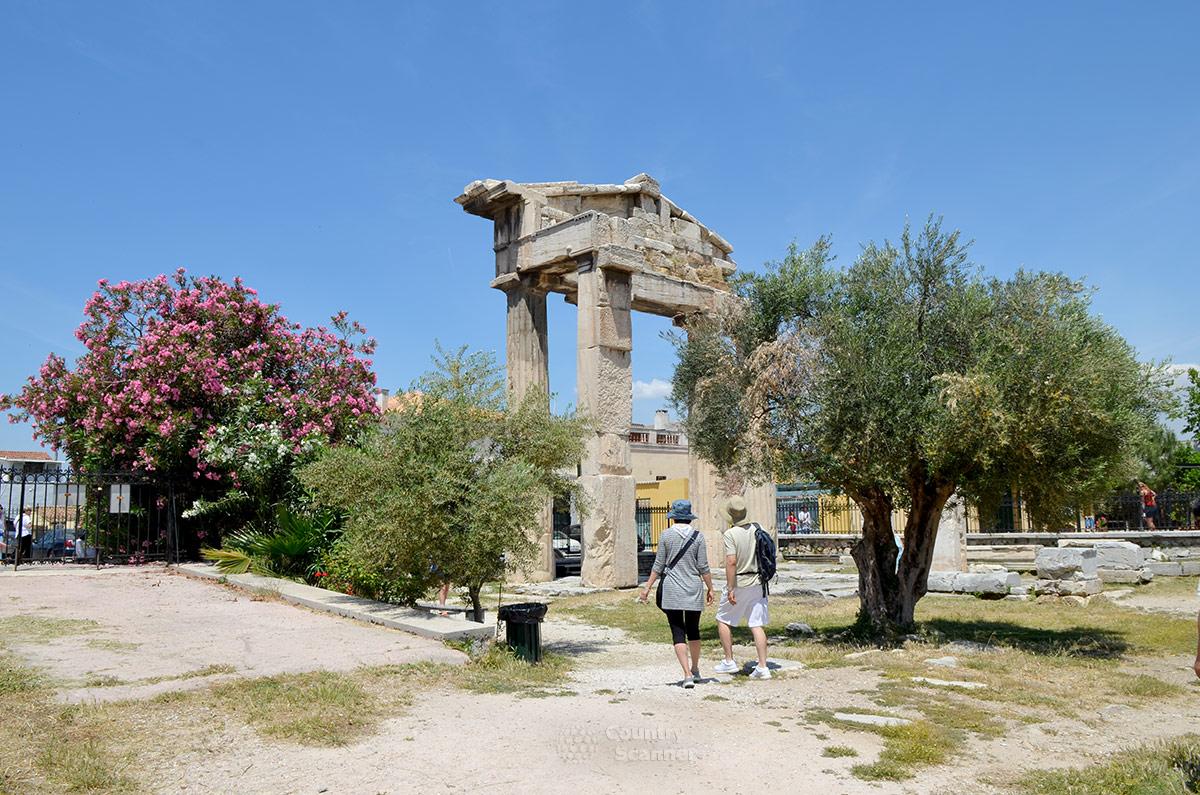 На фоне цветущих растений величественный северный вход в римскую агору смотрится особенно живописно. Отсюда к торговым рядам приходили покупатели многочисленных товаров.