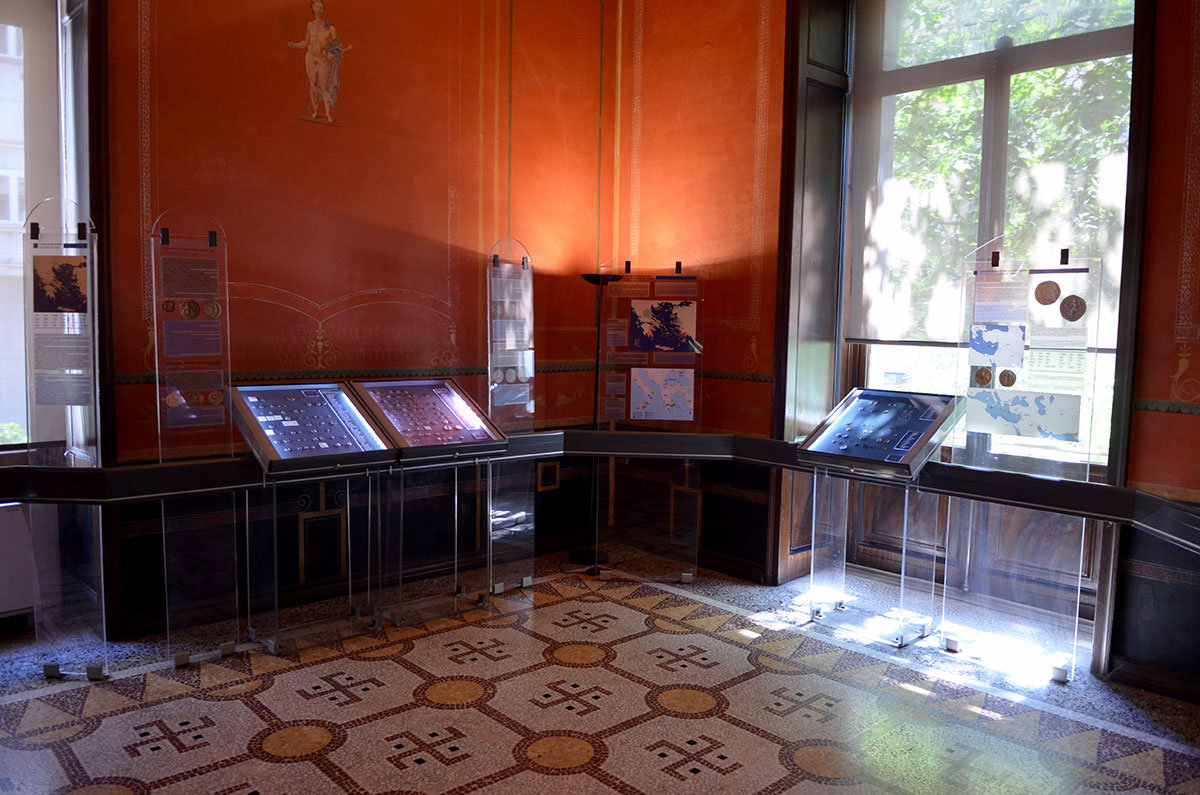 Древние символы свастики, использованные гораздо позднее фашистами, использованы в мозаике полового покрытия в одном из залов афинского музея нумизматики.
