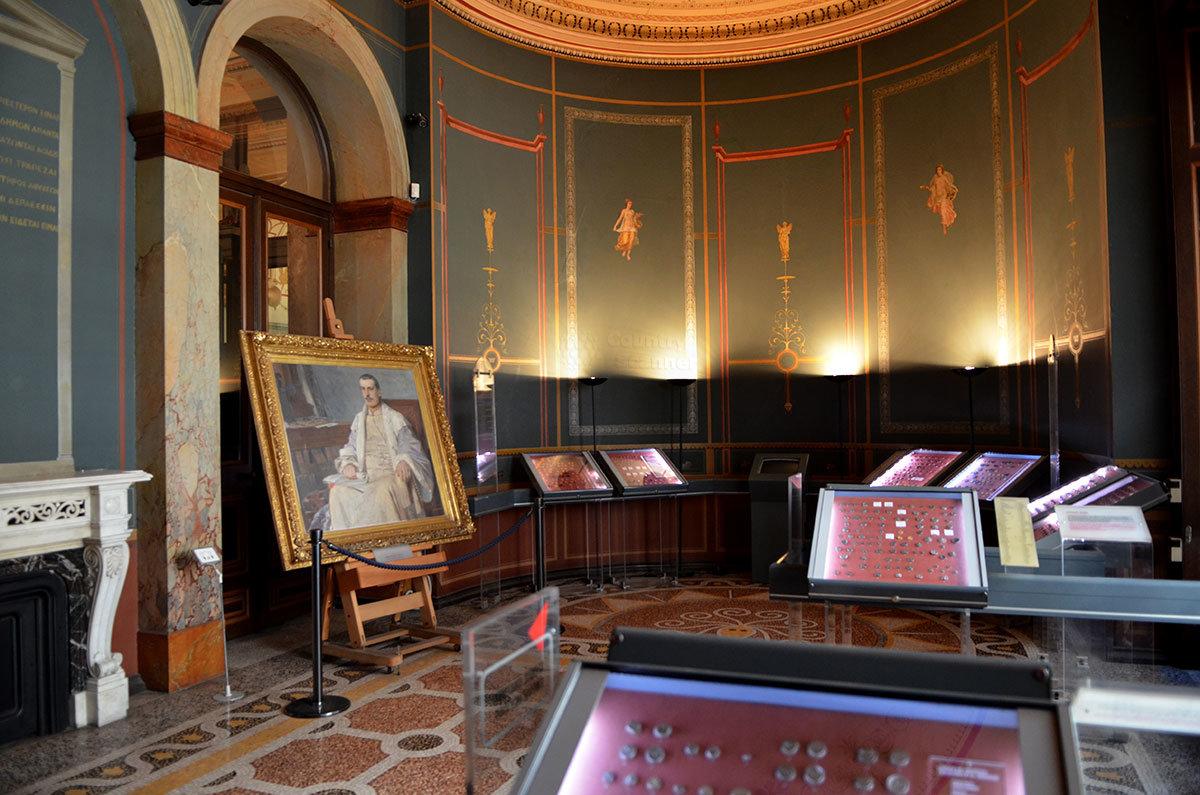 Один из залов афинского музея нумизматики кроме экспонатов содержит живописный портрет бывшего хозяина дворца, археолога Шлимана.