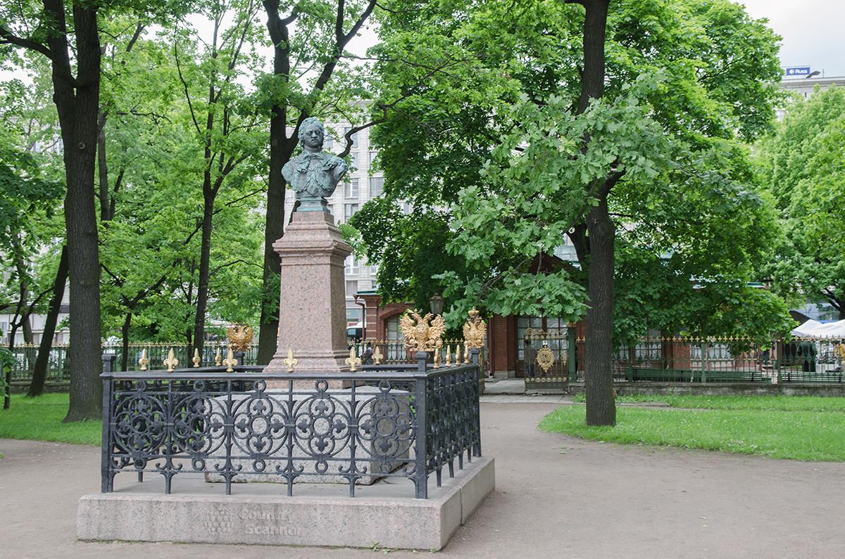Бюст Петра Великого в сквере, на заднем плане лицевая сторона защитного павильона домика Петра в Санкт-Петербурге.