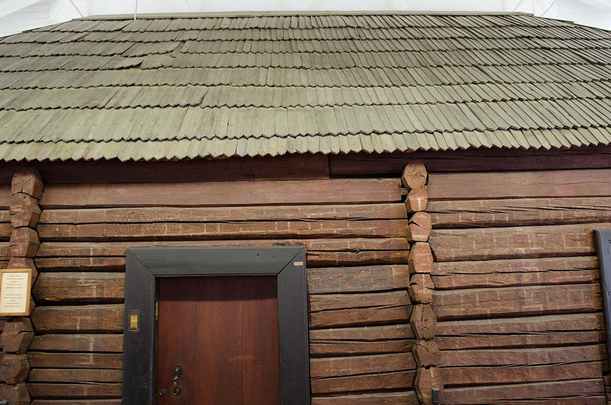 Ракурс, позволяющий подробно рассмотреть стены, дверь и кровлю домика Петра в Санкт-Петербурге.