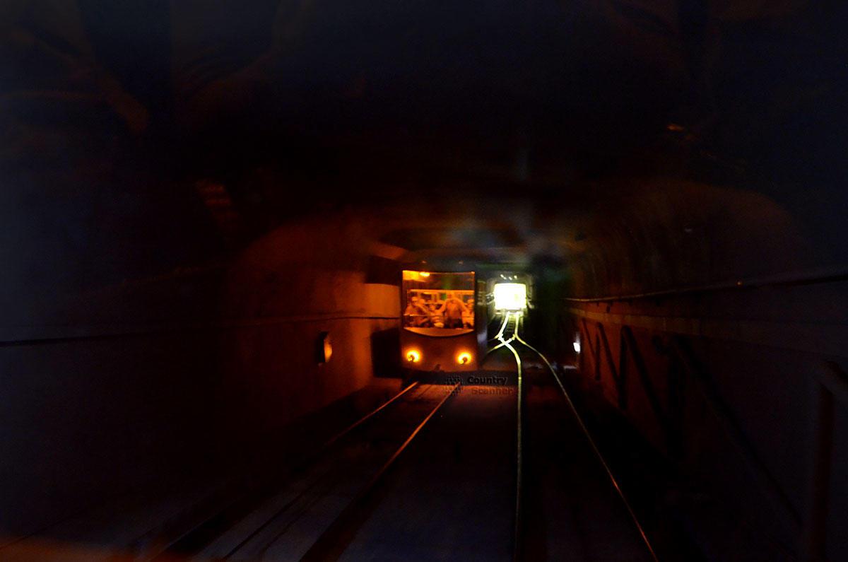 Туннель фуникулера освещается только фарами вагончиков, не считая световой рекламы и иллюминации.
