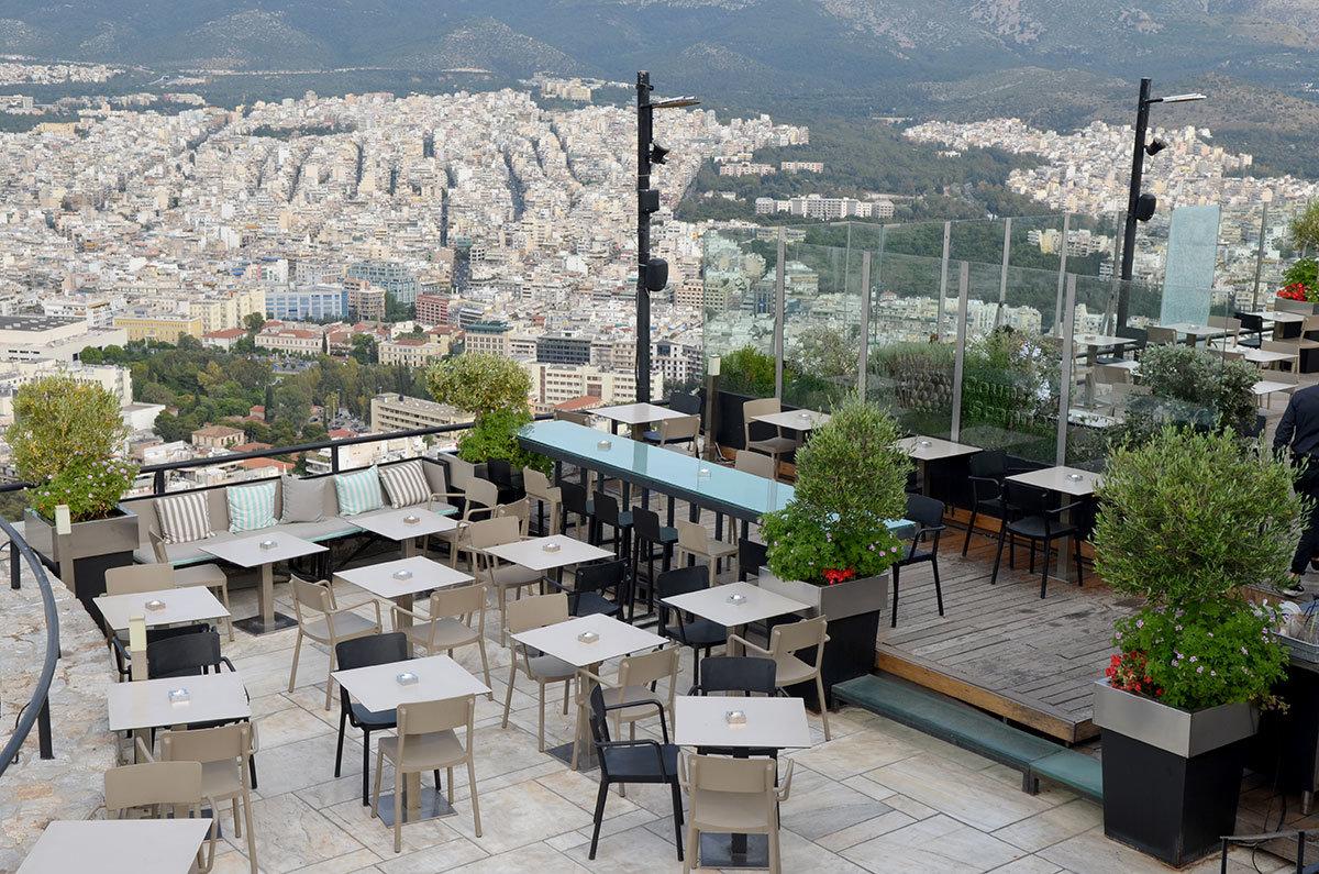 Подготовленные к приему посетителей столики ресторана Оризонт на вершине высочайшего холма в центре Афин – Ликавиттоса, или волчьего.