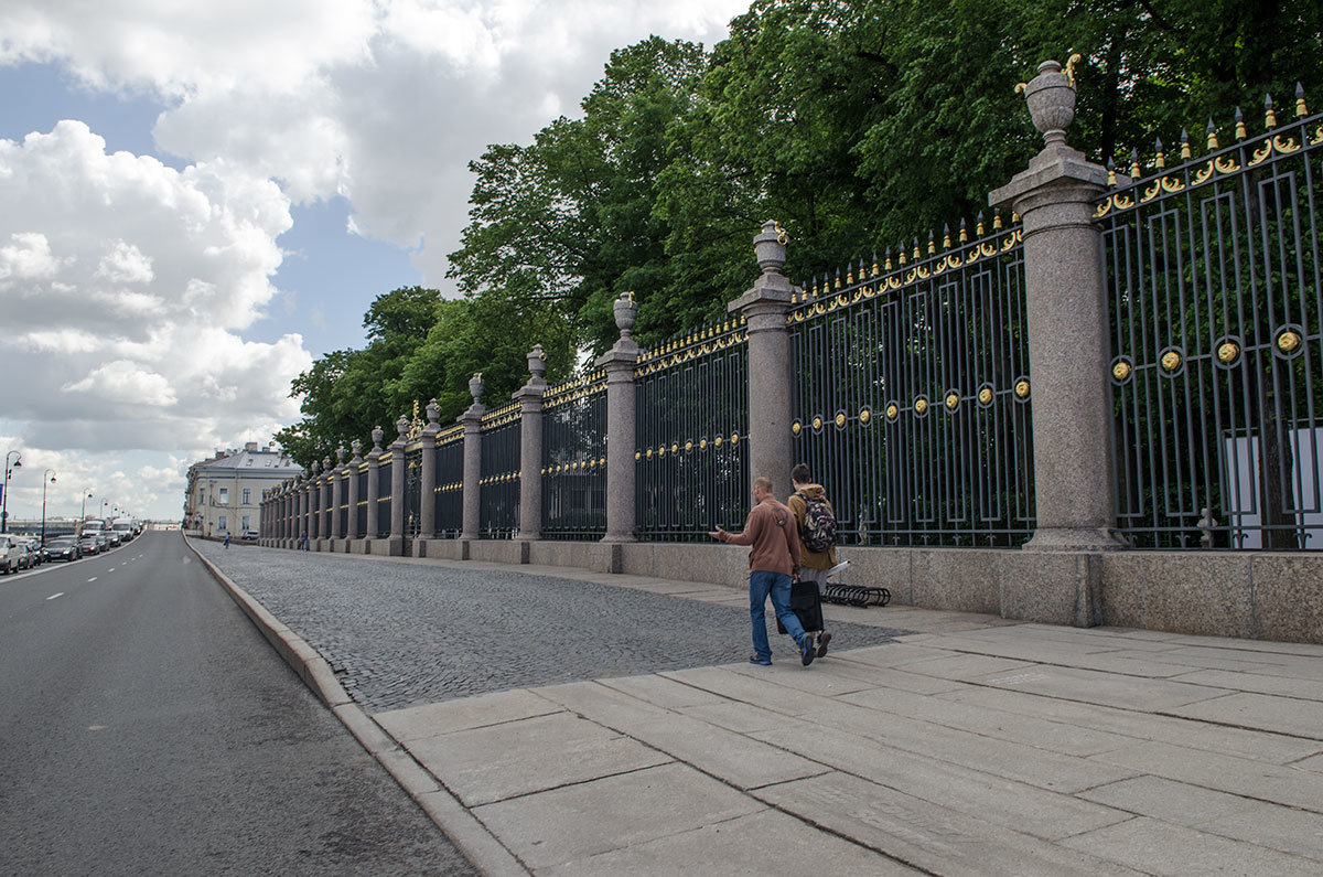 Вид вблизи на ограждение территории летнего сада, мраморное основание и колонны с коваными решетками.