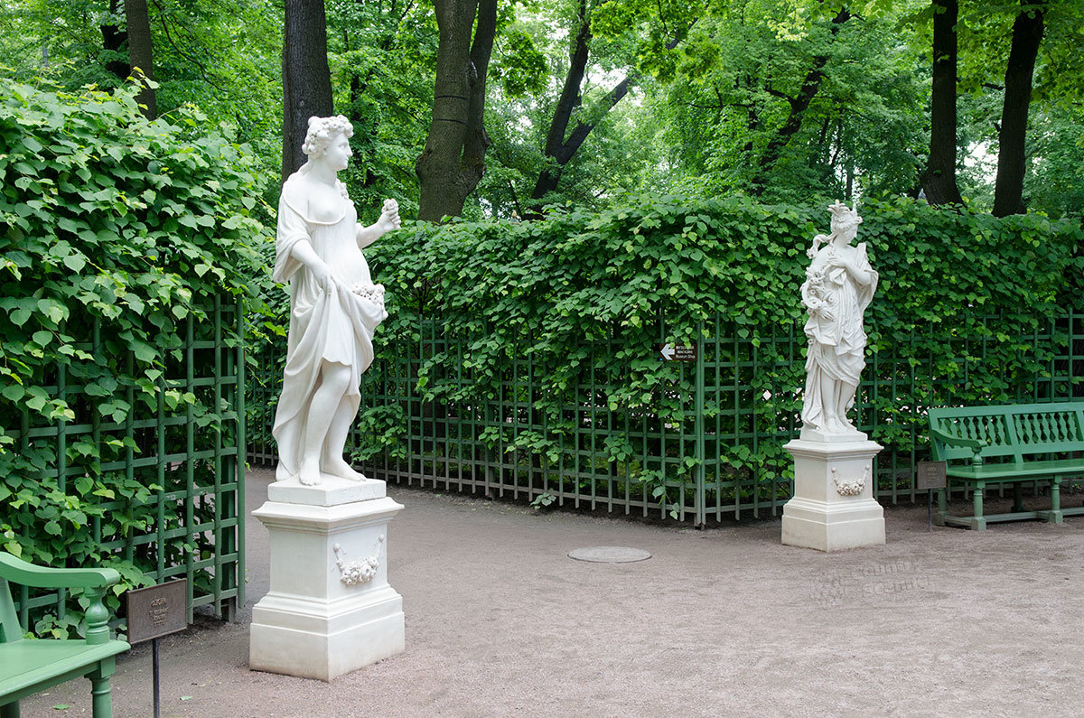 Копии античных скульптур среди зелени летнего сада, рядом с живыми изгородями и парковыми скамейками для отдыха посетителей.