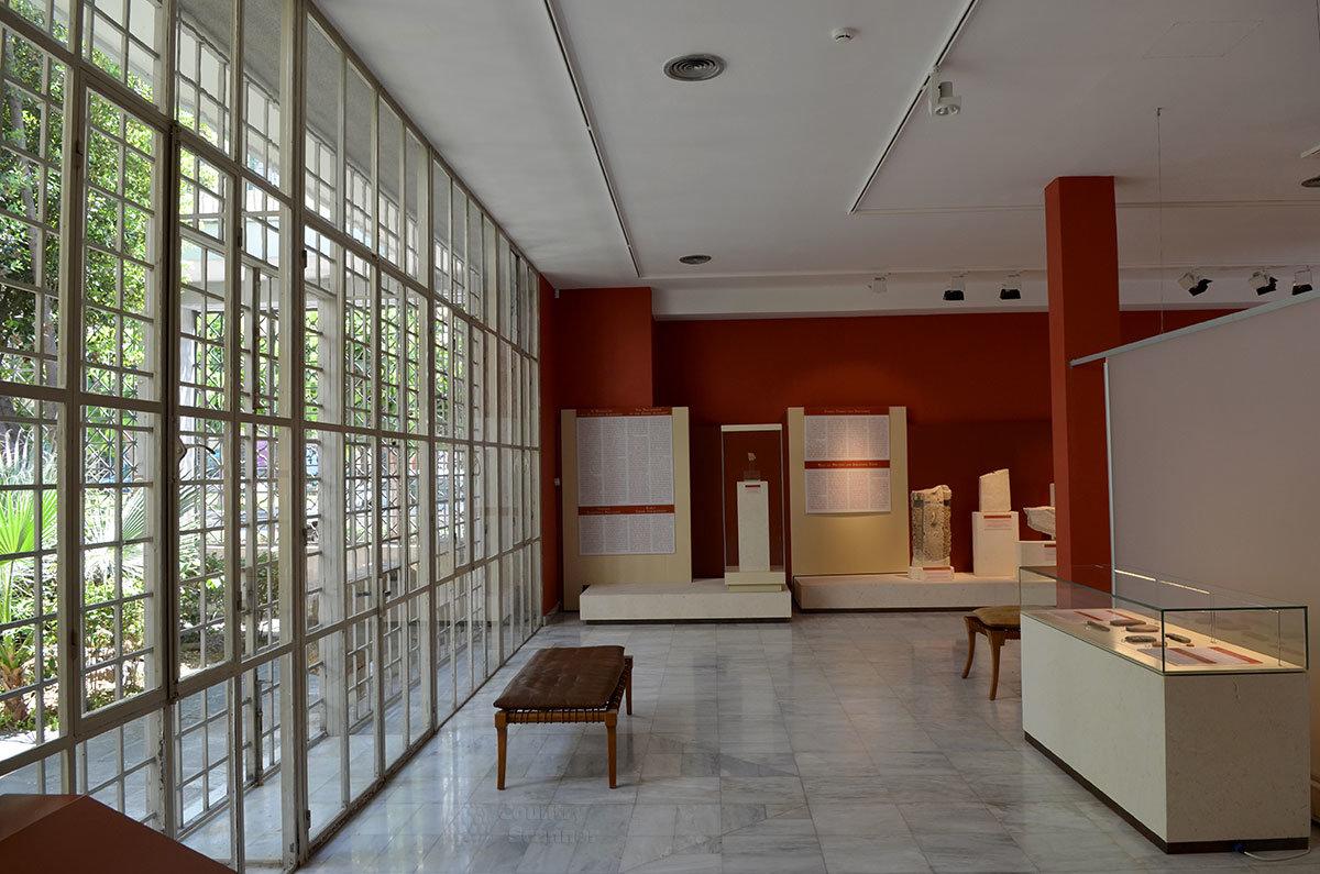 Первый экспозиционный зал музея эпиграфики оформлен в бардовом цвете, одна из стен остеклена и выходит во внутренний двор.