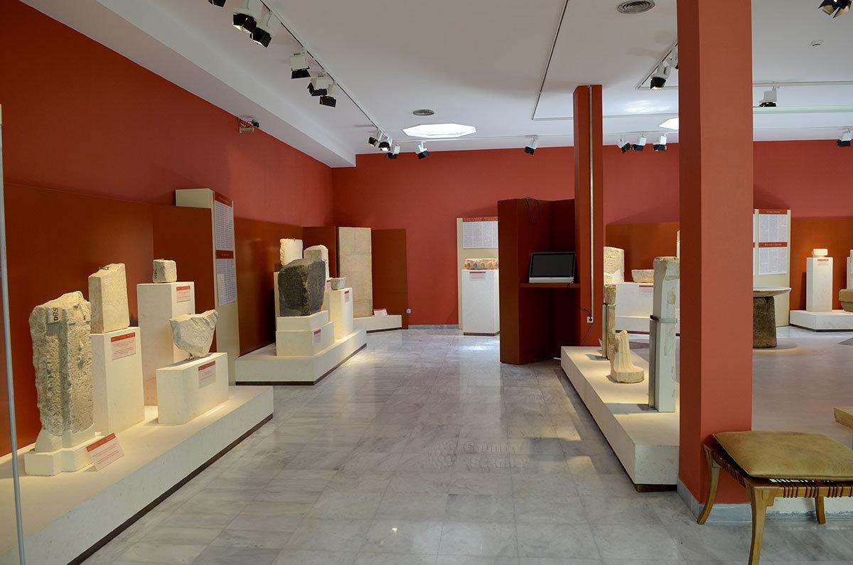 Интерьер выставочного помещения музея эпиграфики и расположенные вдоль стен и в центре крупногабаритные плиты с текстами.