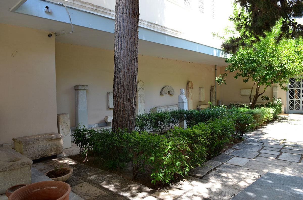 Внутренний двор музея эпиграфики содержит несколько экспонатов, размещенных вдоль наружной стены здания.