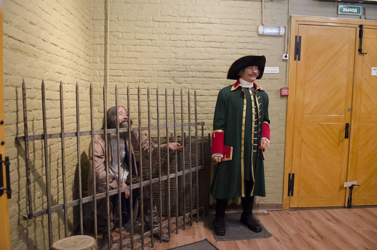 Подозреваемый в совершении преступления и стражник у входа на выставку орудий пыток Средневековья.