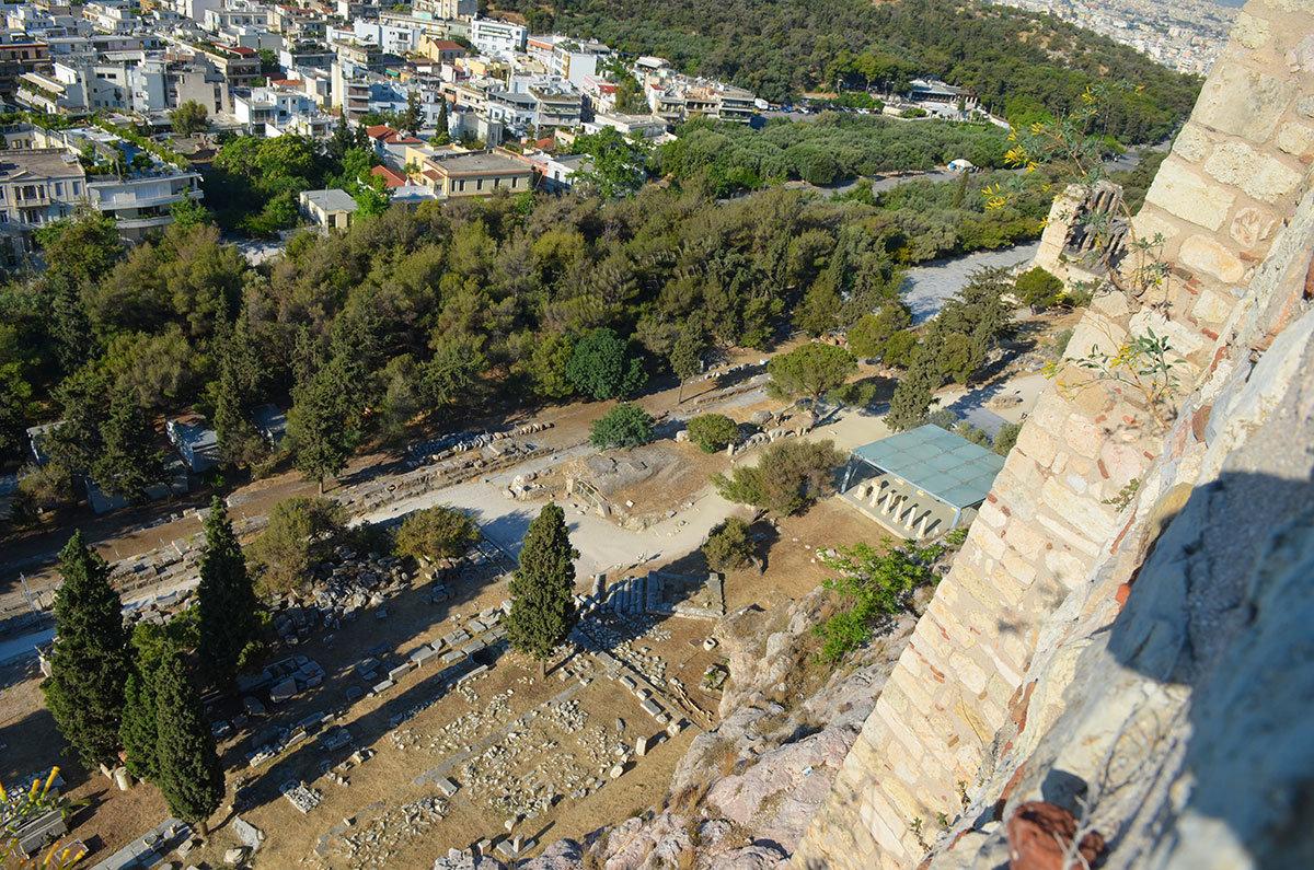 С южного участка стены афинского Акрополя видны нижележащие достопримечательности – развалины Асклепиона и галерея (стоя) Эвмена.