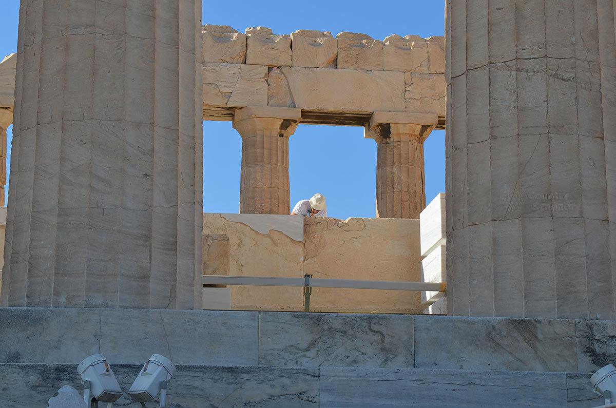 Современный греческий каменщик увлечен восстановительными работами на объекте афинского Акрополя.