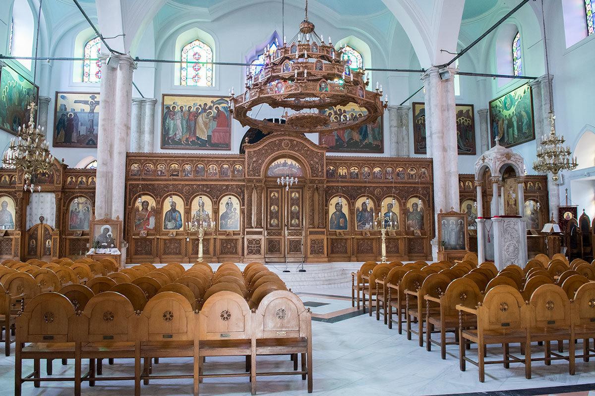 Общий вид иконостаса алтаря собора Святого Тита, деревянная резная люстра и ряды кресел для прихожан, необычные для православия.