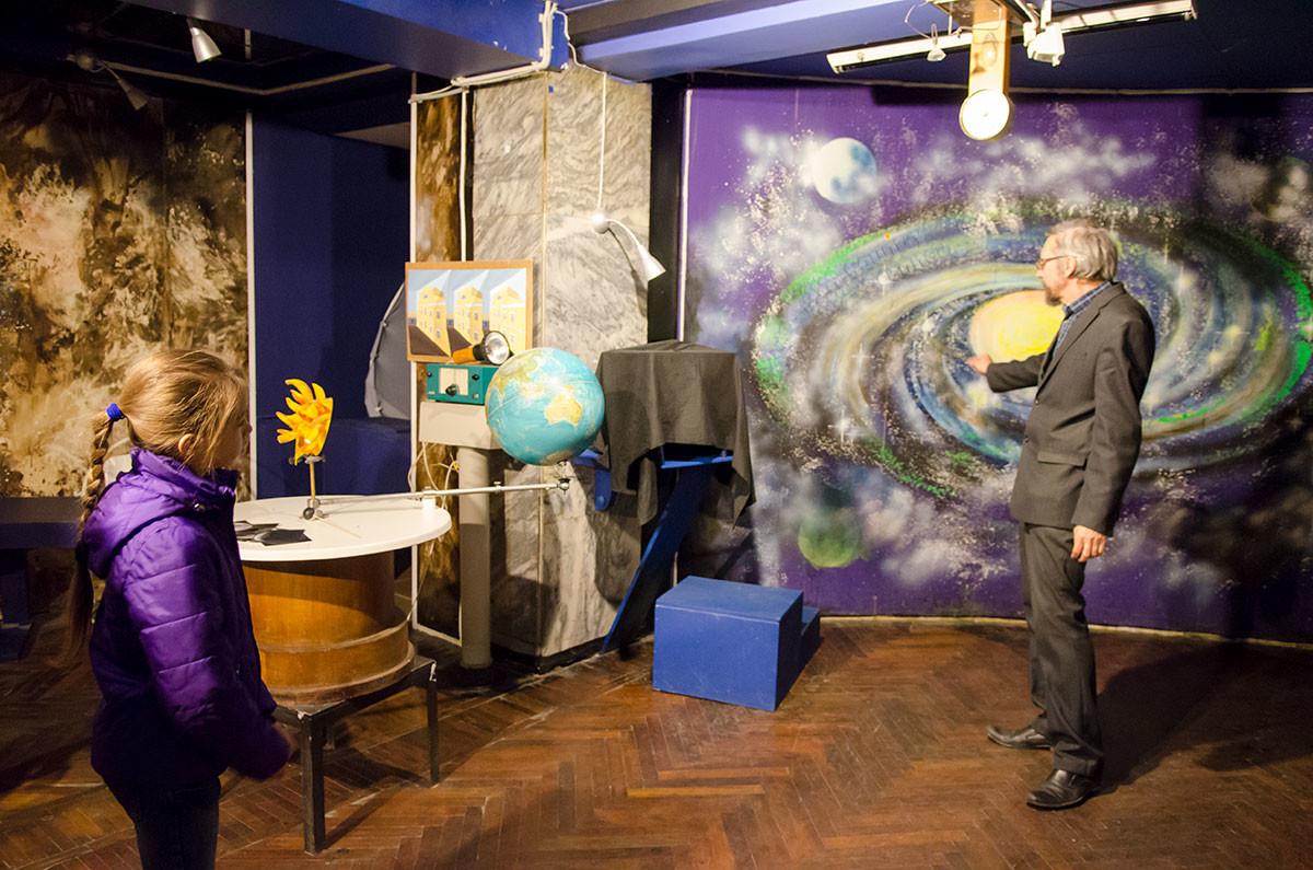 Лектор лаборатории занимательных опытов объясняет школьникам процесс образования планет Солнечной системы.