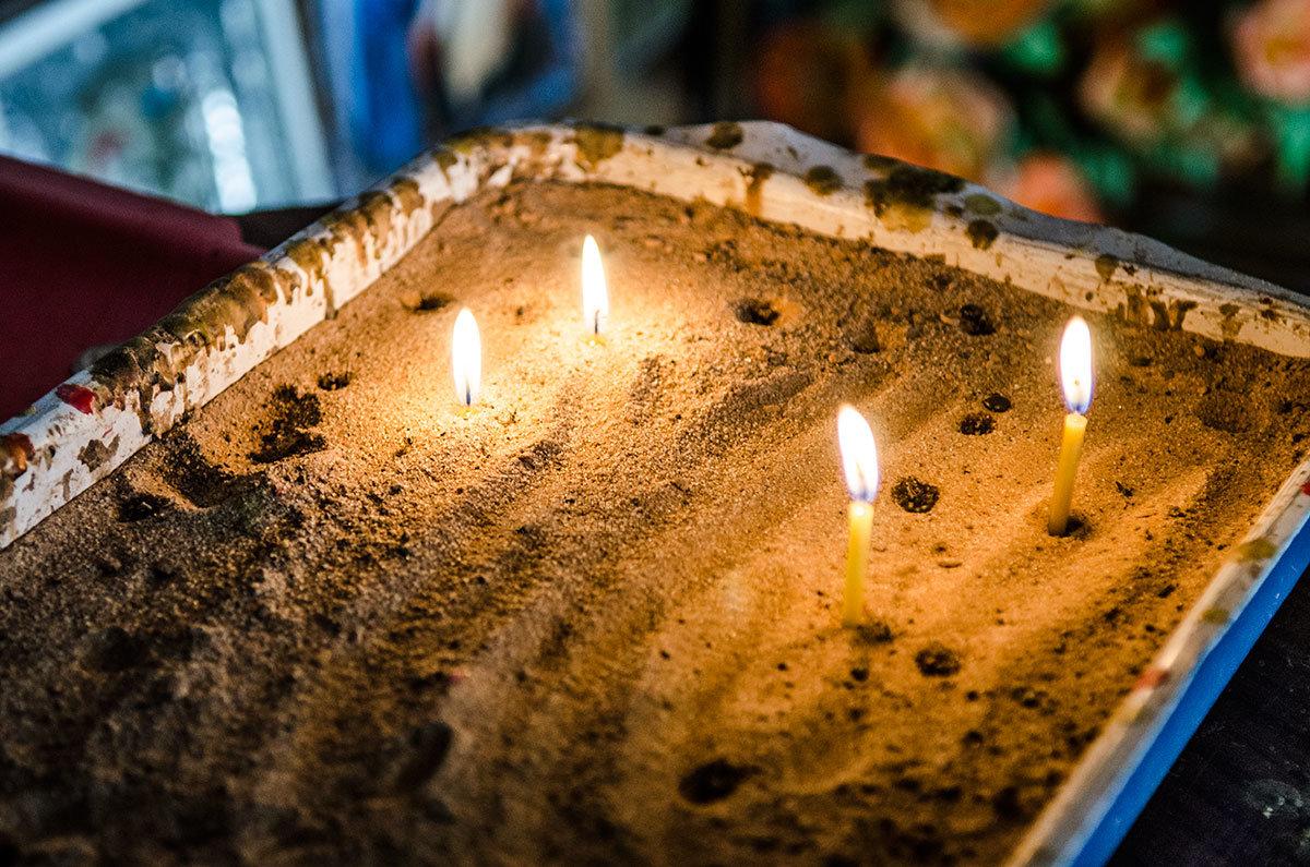 Заздравные свечи в часовне возле источника Текунок устаналливают в емкость с песком, установленную на самодельном подсвечнике.