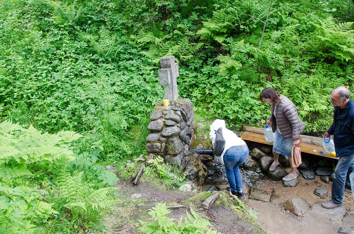 Высеченный из камня крест, установленный на каменной стенке из глыб, отмечает выход воды источника Текунок.