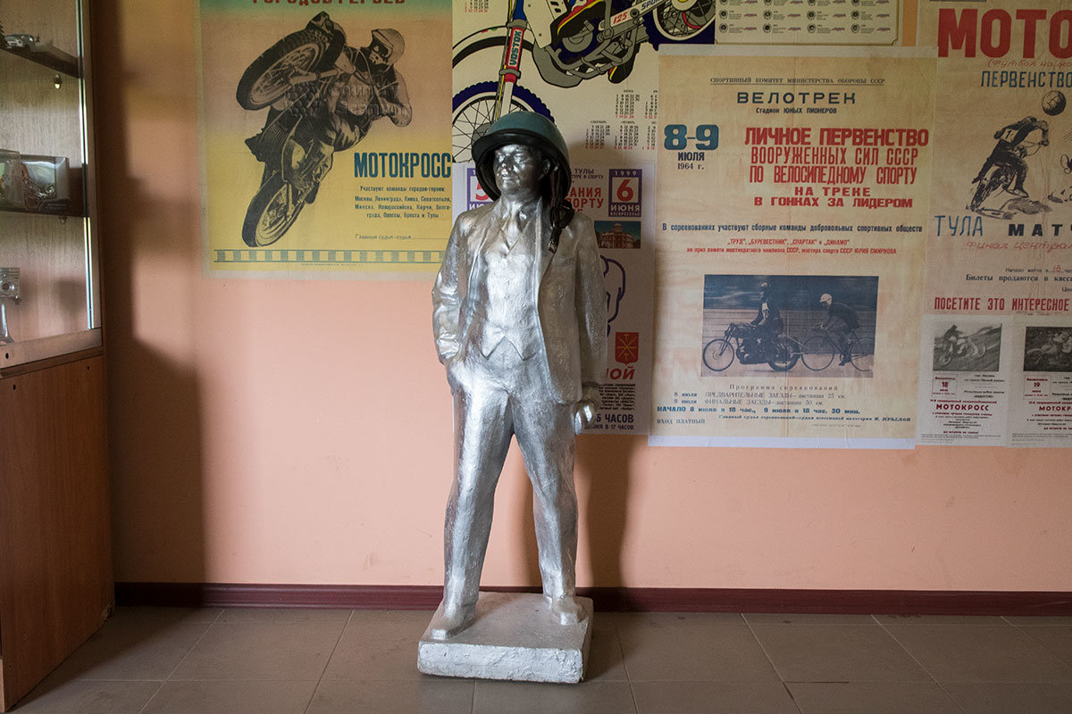 Вестибюль тульского мотомузея оклеен многочисленными афишами с анонсами спортивных и развлекательных мероприятий, здесь же статуя Ленина в мотошлеме.