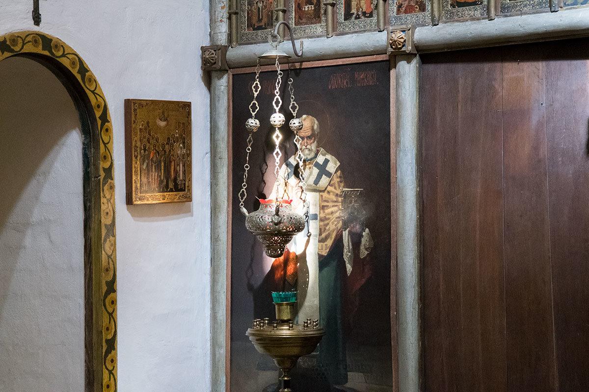 Лампада и подсвечник перед иконой Николая Чудотворца в правой части иконостаса церкви Спаса Нерукотворного усадьбы Абрамцево.
