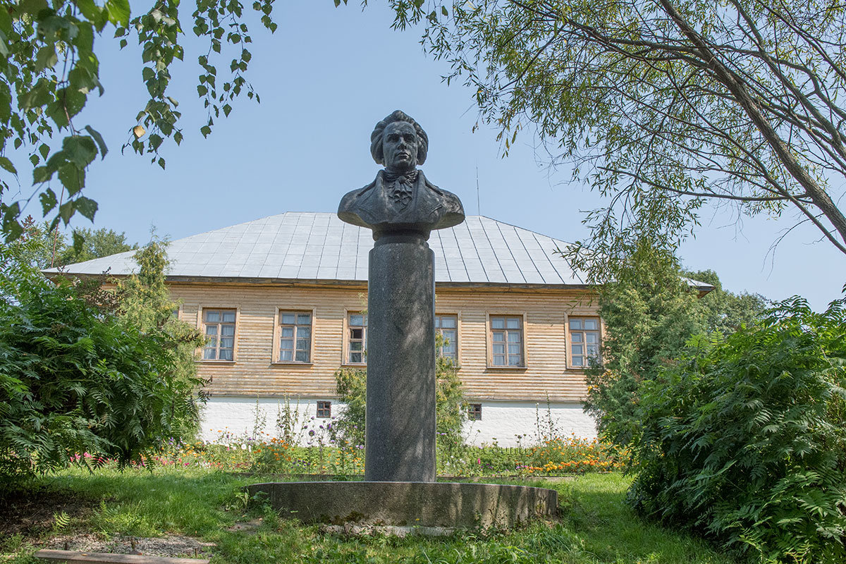 Вид на бюст Андрея Тимофеевича на фоне родового дома в усадьбе Болотова со стороны посадок.