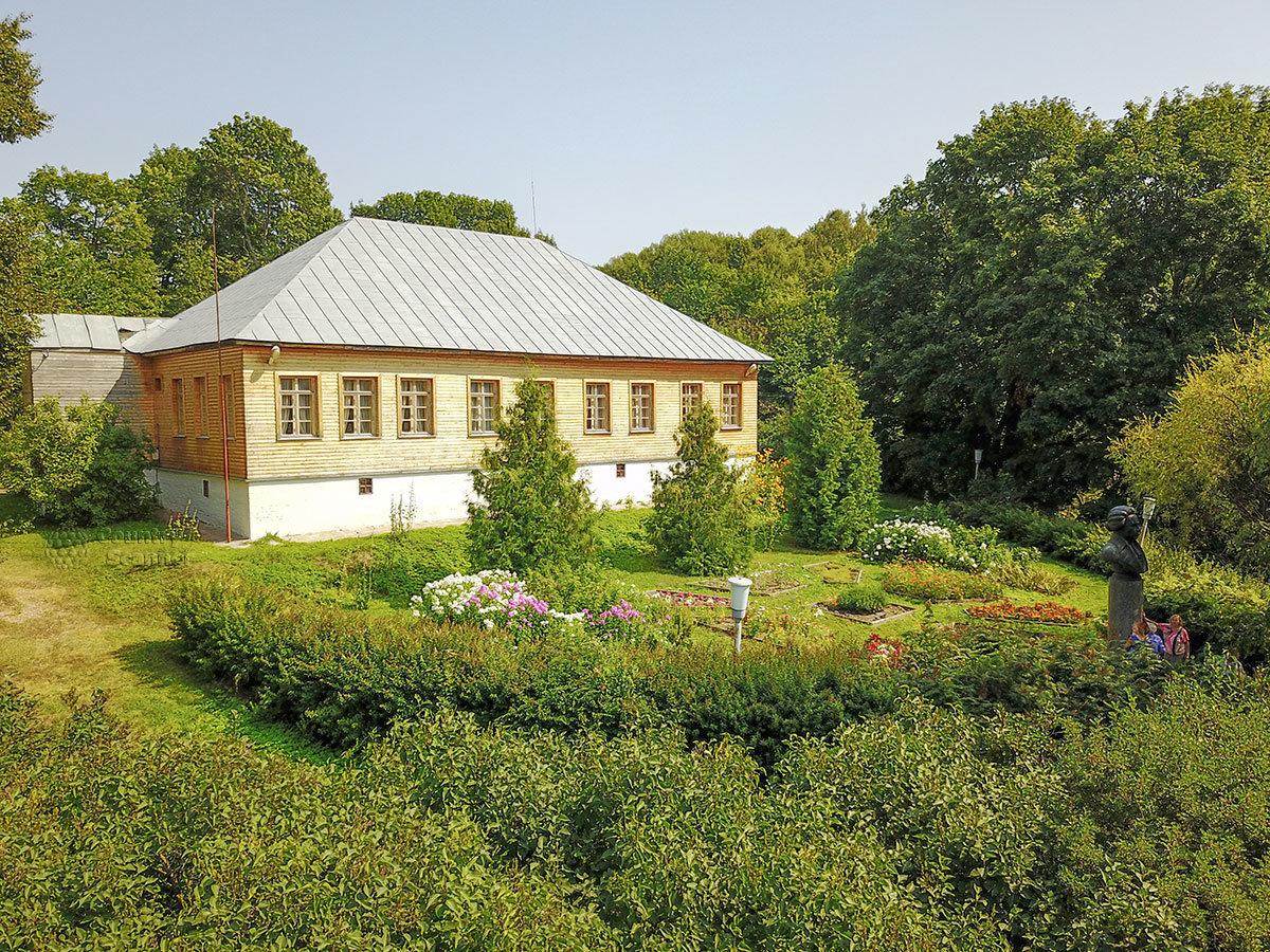 Задний фасад здания, внутренний двор с цветником и окружающей растительностью, памятник выдающемуся ученому и писателю в родовой усадьбе Болотова.