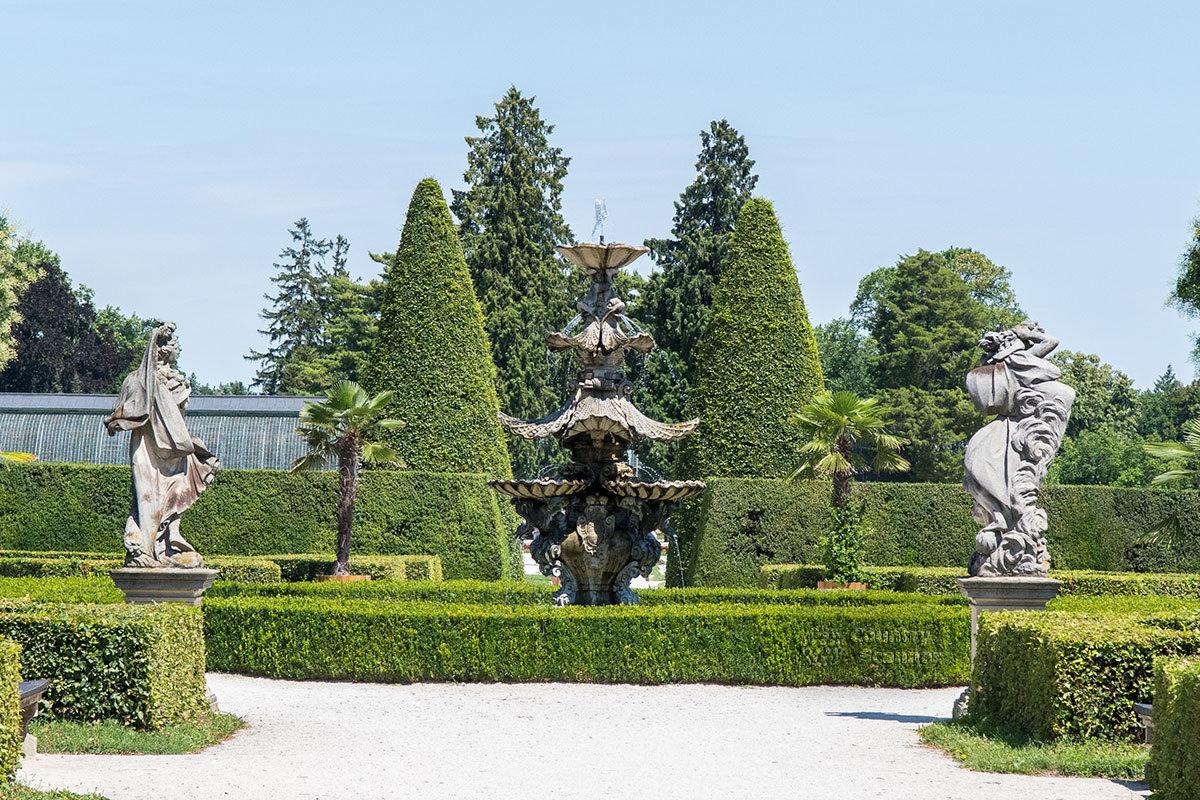 Один из живописных видов в парке замка Леднице со стриженными живыми изгородями и сформированными в конуса кронами деревьев.