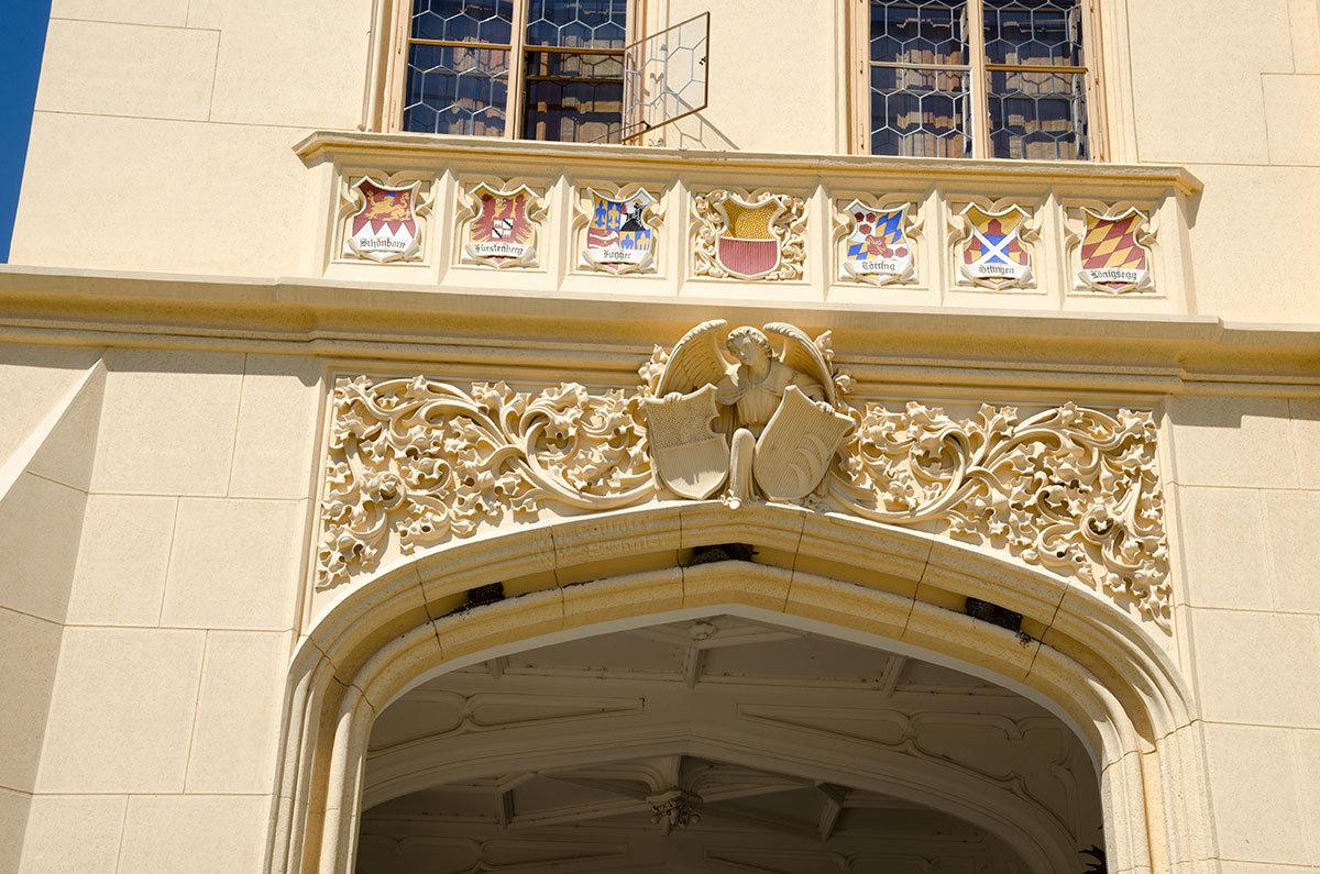 Входная арка здания замка Леднице украшена орнаментом с фигуркой коленопреклоненного ангела и щитами с гербами семейств, родственных бывшим владельцам.
