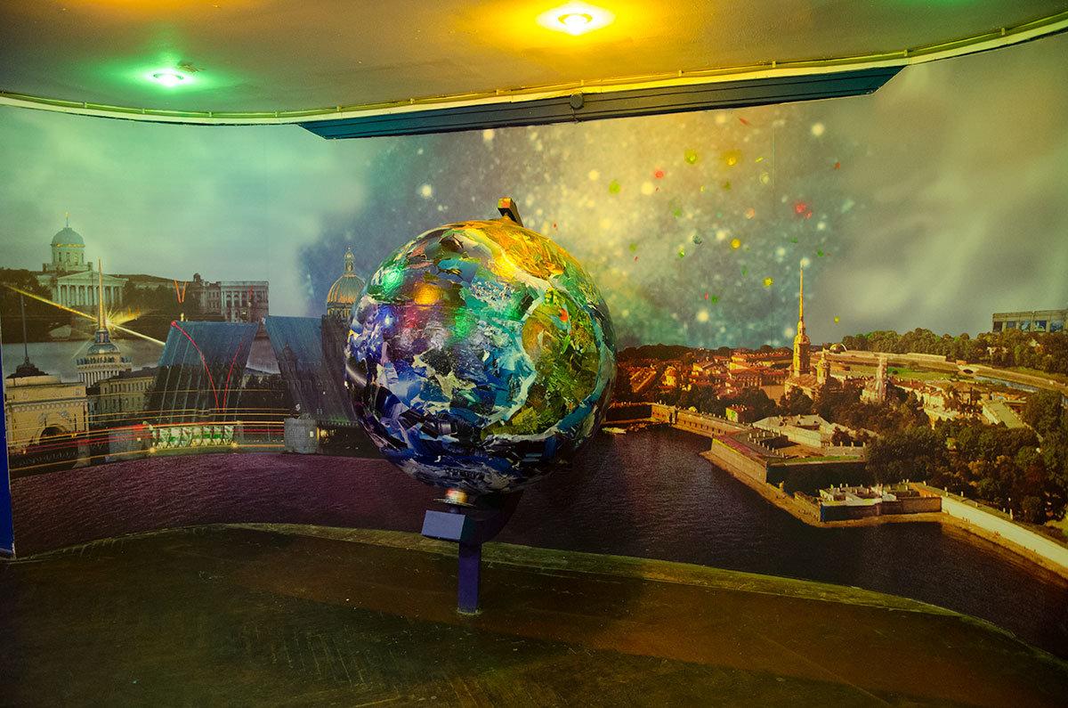Планетарий в Санкт-Петербурге демонстрирует модель земного шара и городские достопримечательности на фоне звездного неба.