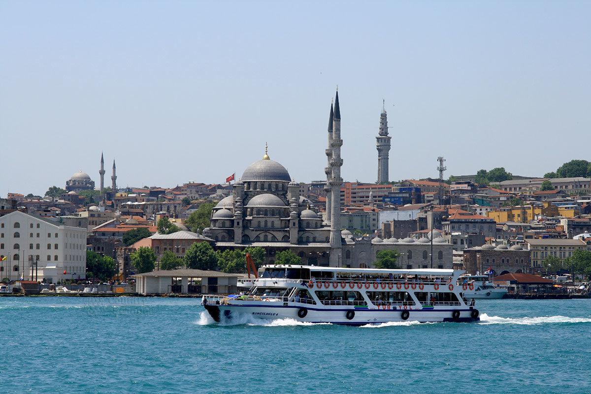 Демонстрирующий туристам пролив Босфор прогулочный теплоход на фоне городских кварталов и сразу нескольких мечетей.