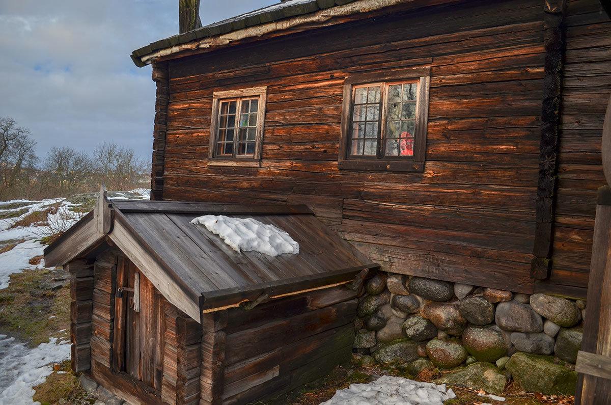 Одно из деревянных строений в музее Скансен и собачья будка рядом, почему-то закрытая на висячий замок.