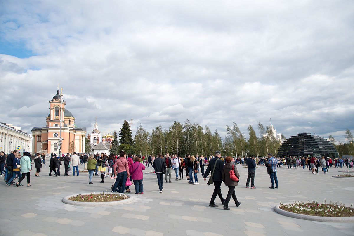 Через западный вход в парк Зарядье посетители проходят на просторную площадь с множеством круглых цветочных клумб.