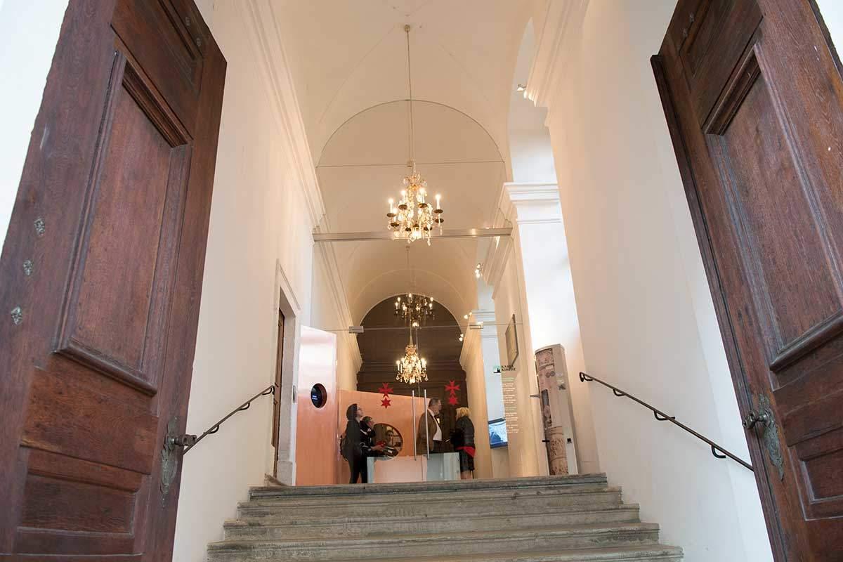 Крутая лестница подъема внутрь Карлскирхе ведет к прозрачной стеклянной двери, на которой нанесены символы рыцарского ордена.