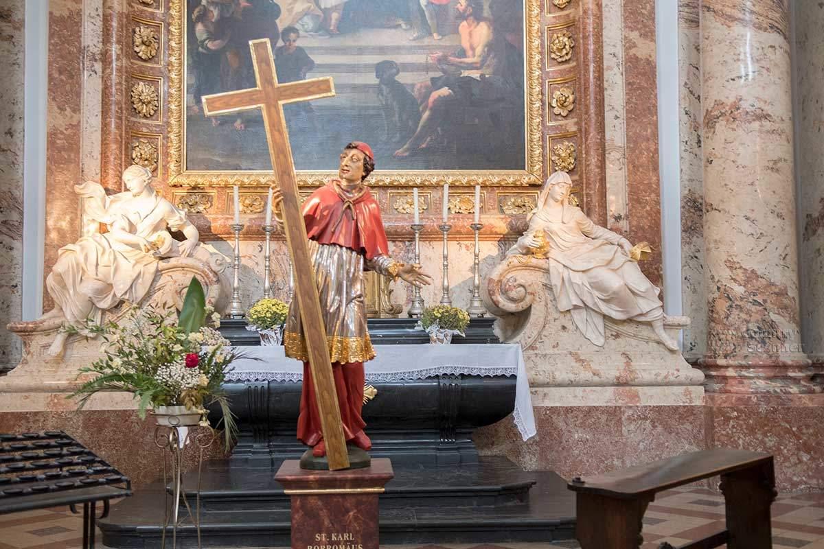 Раскрашенная скульптура Карла Борромео с крестом – один из декоративных и религиозных элементов Карлскирхе.