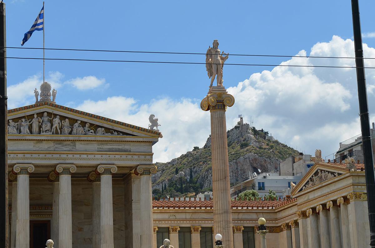 Афинская академия и колонна с фигурой Аполлона привлекательно смотрятся на фоне одного из холмов греческой столицы.
