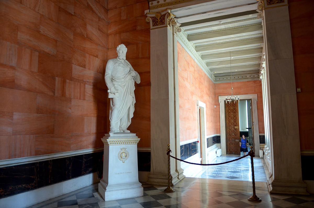 Скульптура финансировавшего строительство здания предпринимателя и мецената Симона Синаса украшает вестибюль Афинской академии.