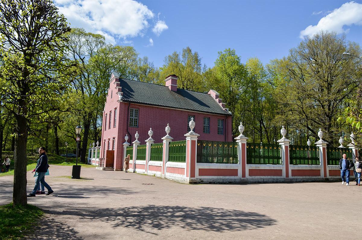 Традиционный для Нидерландов голландский домик в Кусково, ограда территории и близлежащий водоем.