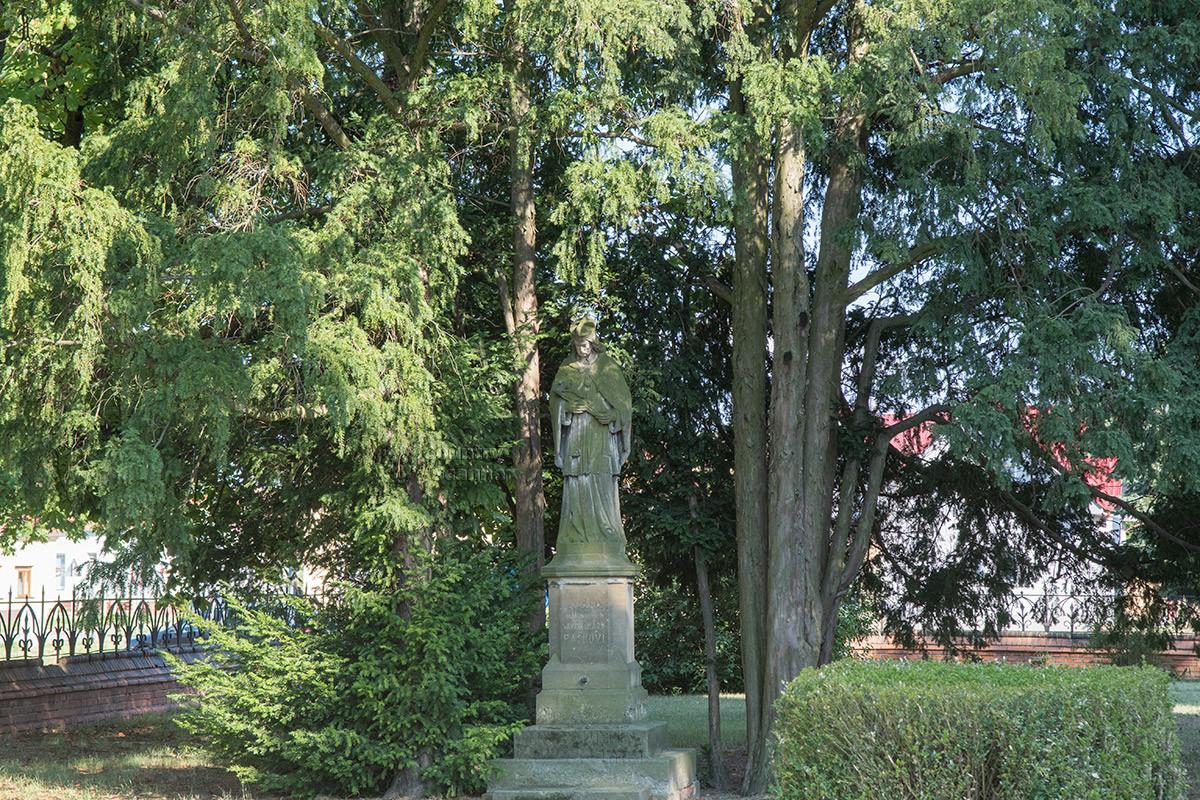 Храм Посещения Пресвятой Девы Марии окружен деревьями, среди которых размещены статуи.