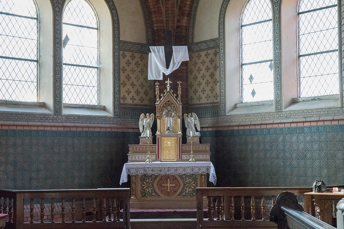 Один из боковых алтарей храма Посещения Пресвятой Девы Марии расположен справа от скамеек для прихожан.