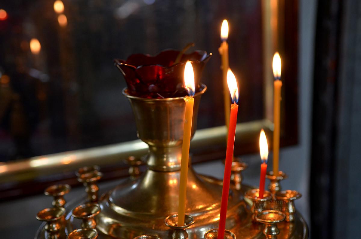 Ближний план заздравных свечей в церкви Спаса Всемилостивого, отражение пламени в бронзе – красивое зрелище.